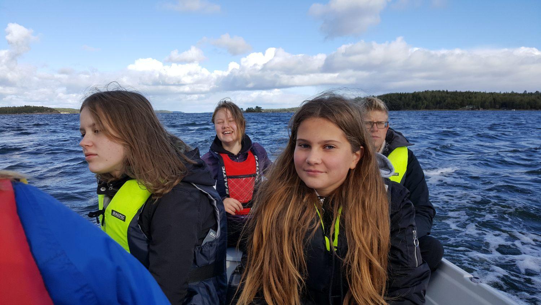 På vägen hem från Apagrundet styr Olga Åberg med biolgoiläraren Peter Rönnberg bredvid sig. Närmast kameran sitter Elin Kari från Kyrkbackens skola i Nagu. Foto: Carina Holm