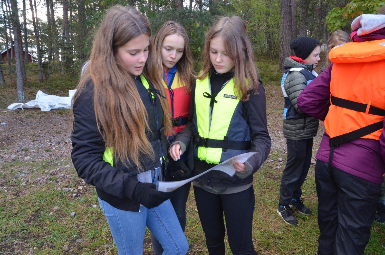 Nagueleverna Elin Kari, Linnea Nordqvist och Frida Hausen tar en titt på sjökortet innan de sätter sig i båten och styr mot Apagrundet. Foto: Carina Holm