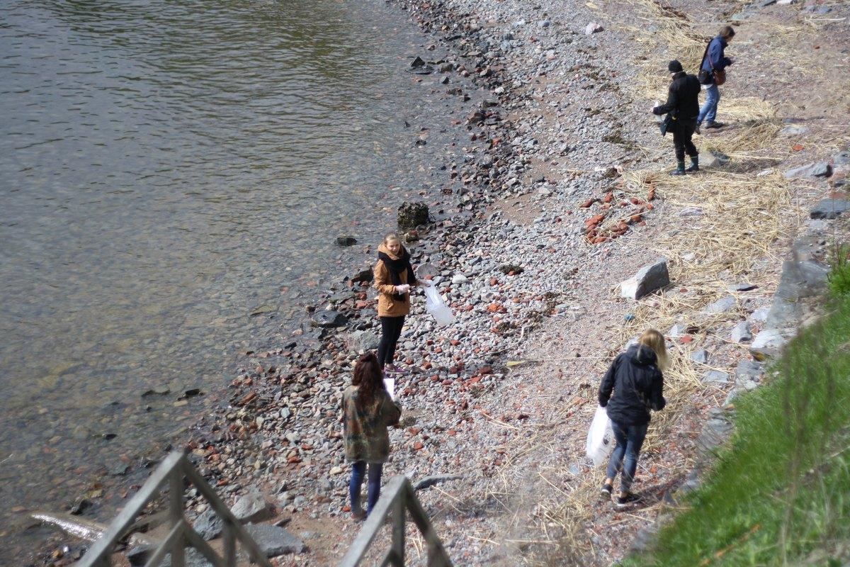 Ungdomar städar en strand