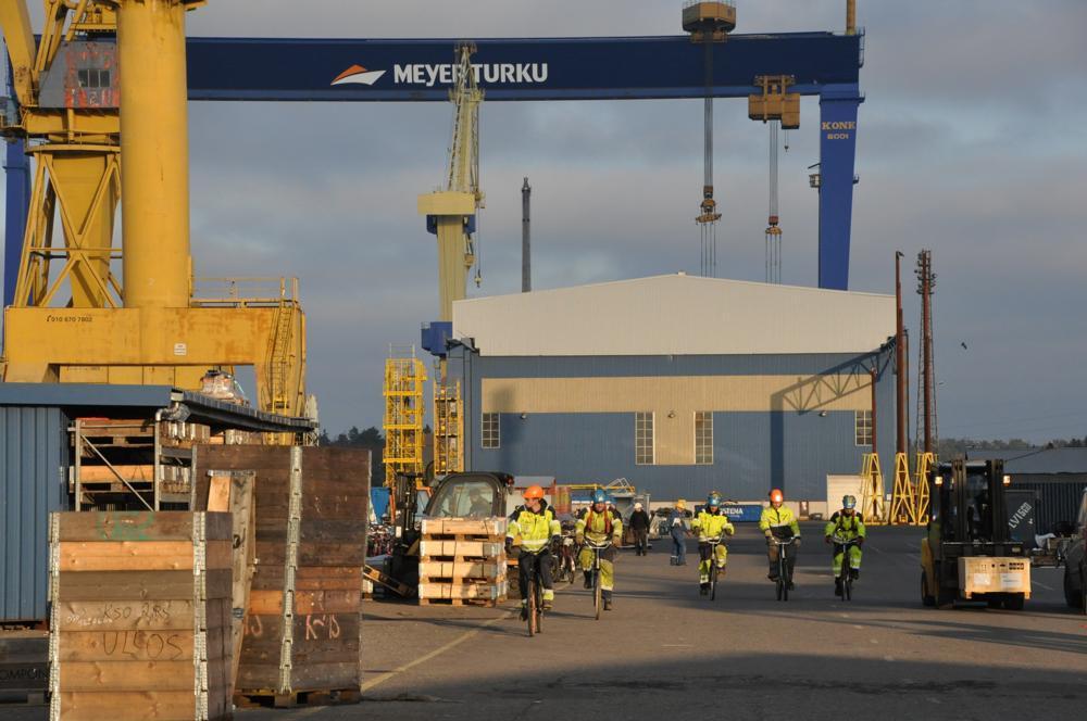 Varvsarbetare åker cykel på varvsområdet vid varvet Meyer Turku i Åbo