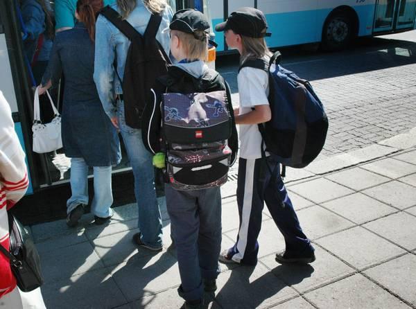 Skolbarn stiger in i en buss, med ryggsäckar på ryggen.