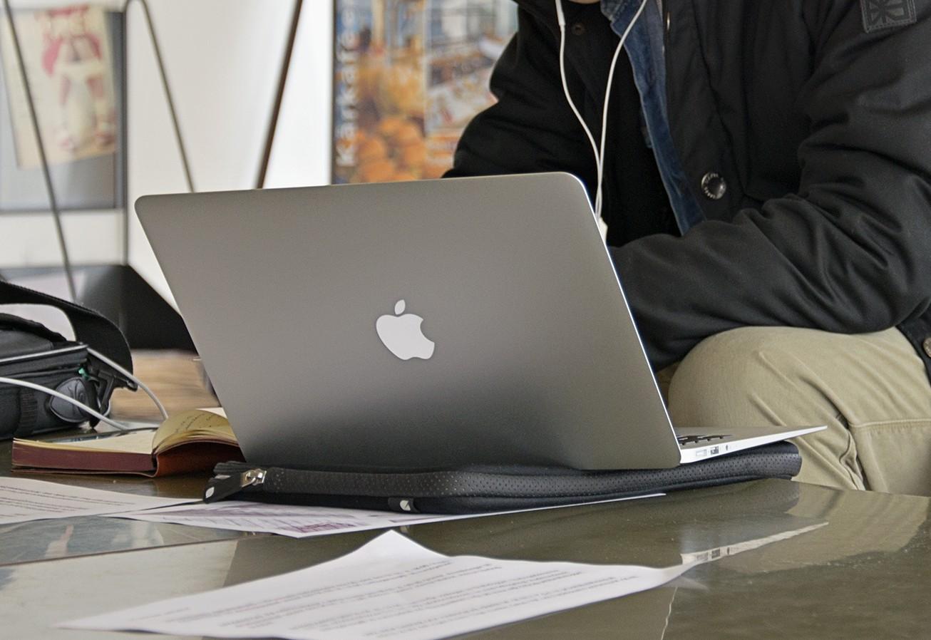 Några papper och en dator på ett bord samt överkroppen av personen som sitter vid datorn.