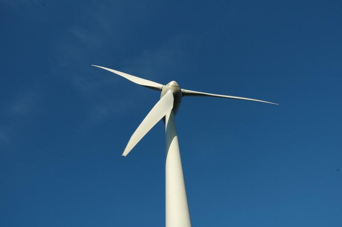 Vindkraftverk fotat nerifrån mot blå himmel