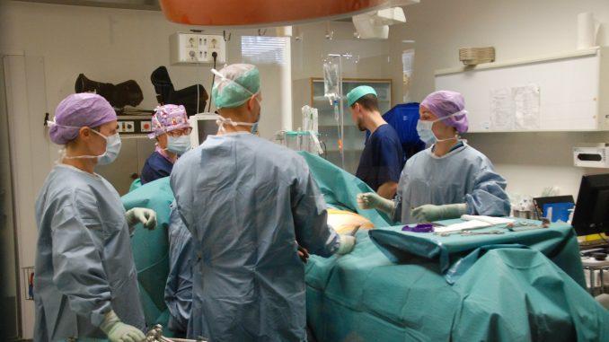 Fem kirurger klädda i skyddskläder står runt ett operationsbord.