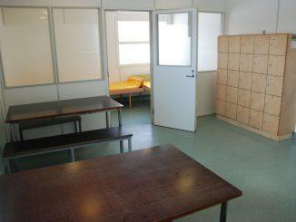 Ett tomt rum med en brits och två bord med bänkar.
