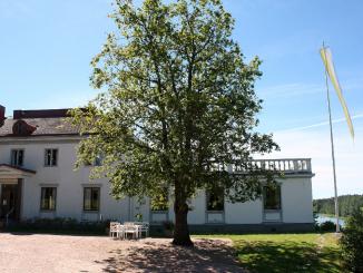 Stor vit byggnad med flygel, blå himmel, grönt träd i förgrunden