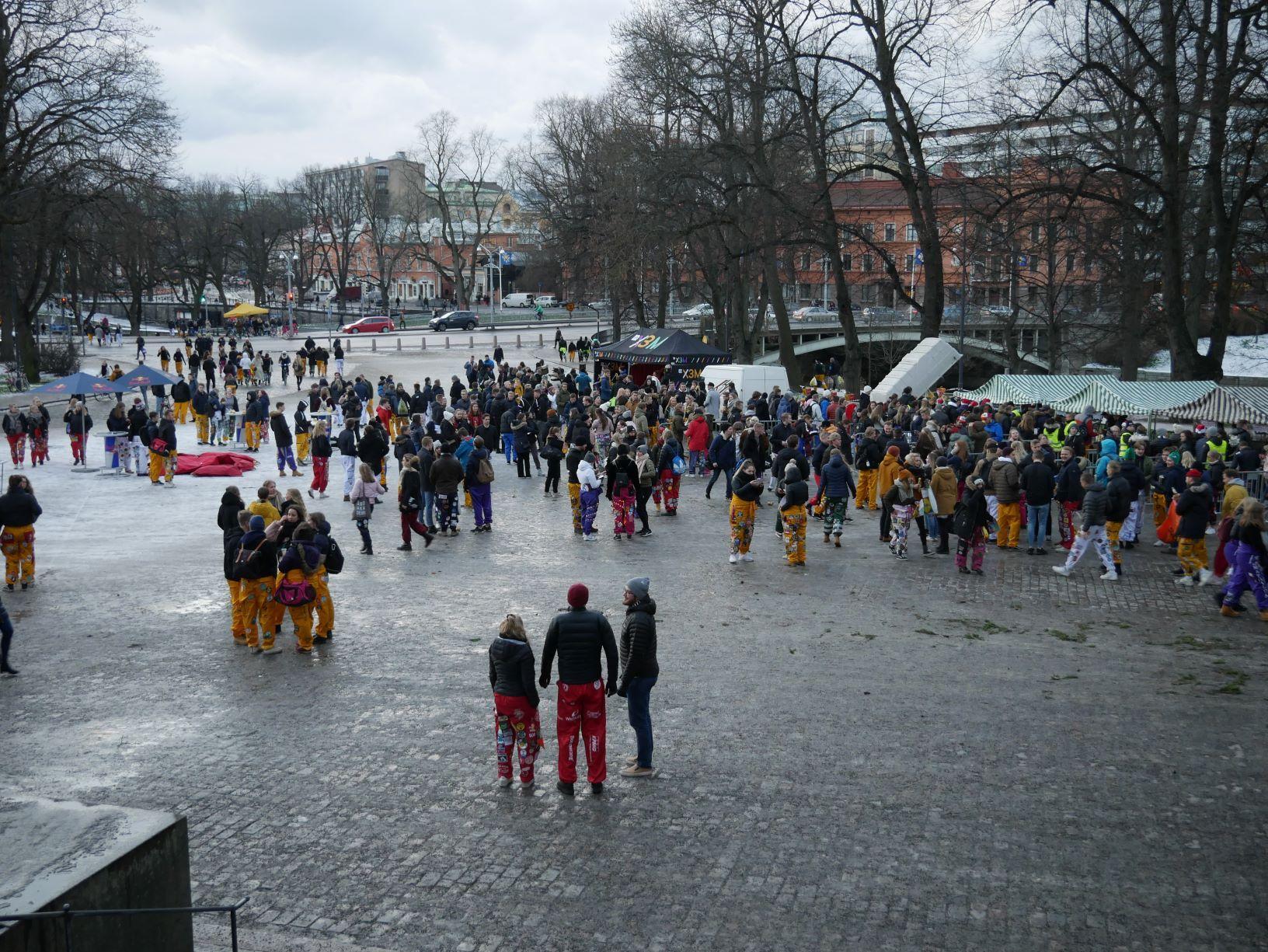 Domkyrkotorget i Åbo fyllt med personer klädda i halare i olika färger. Vädret är grått.