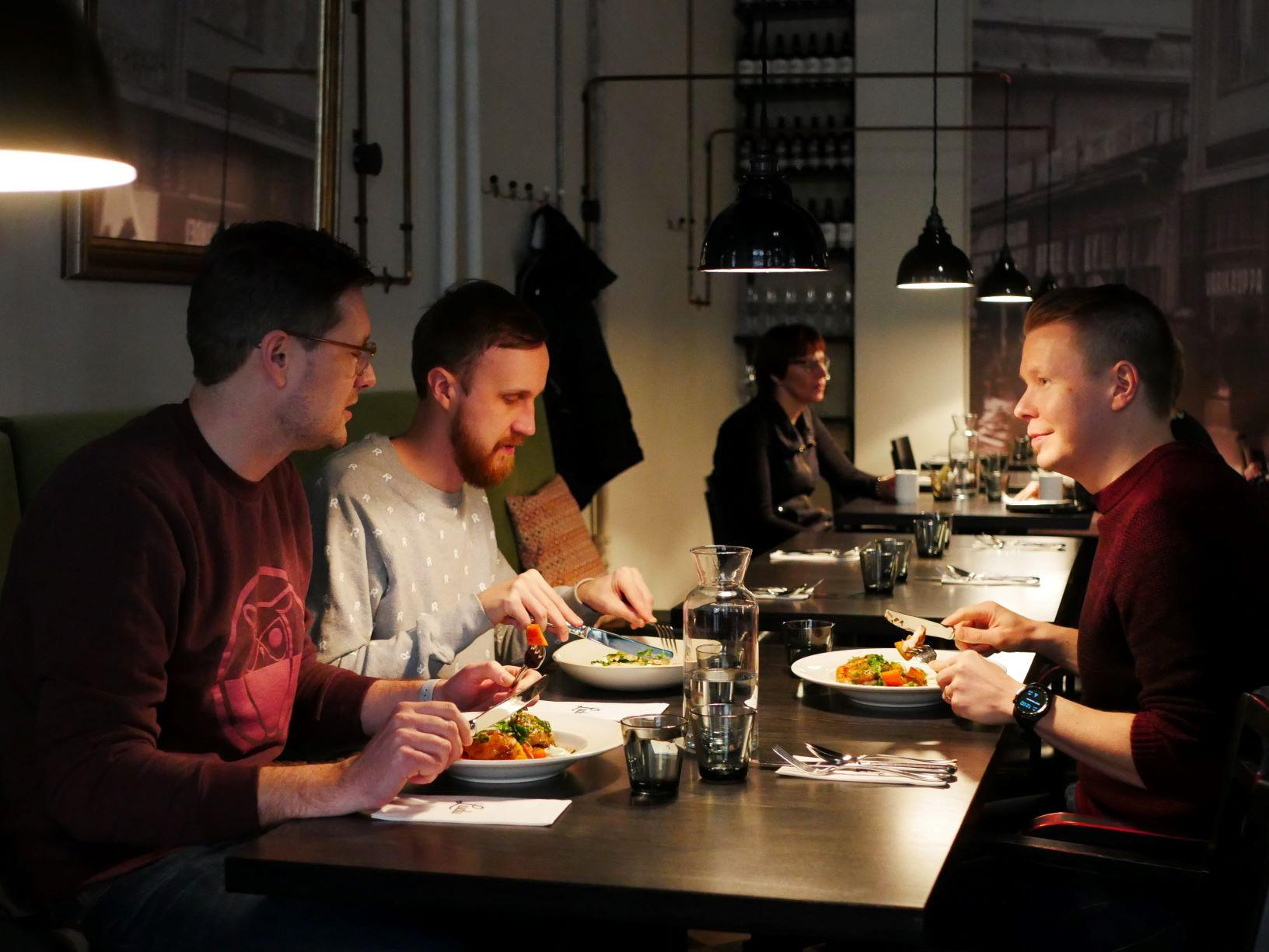 Tre personer sitter vid ett bord på en restaurang