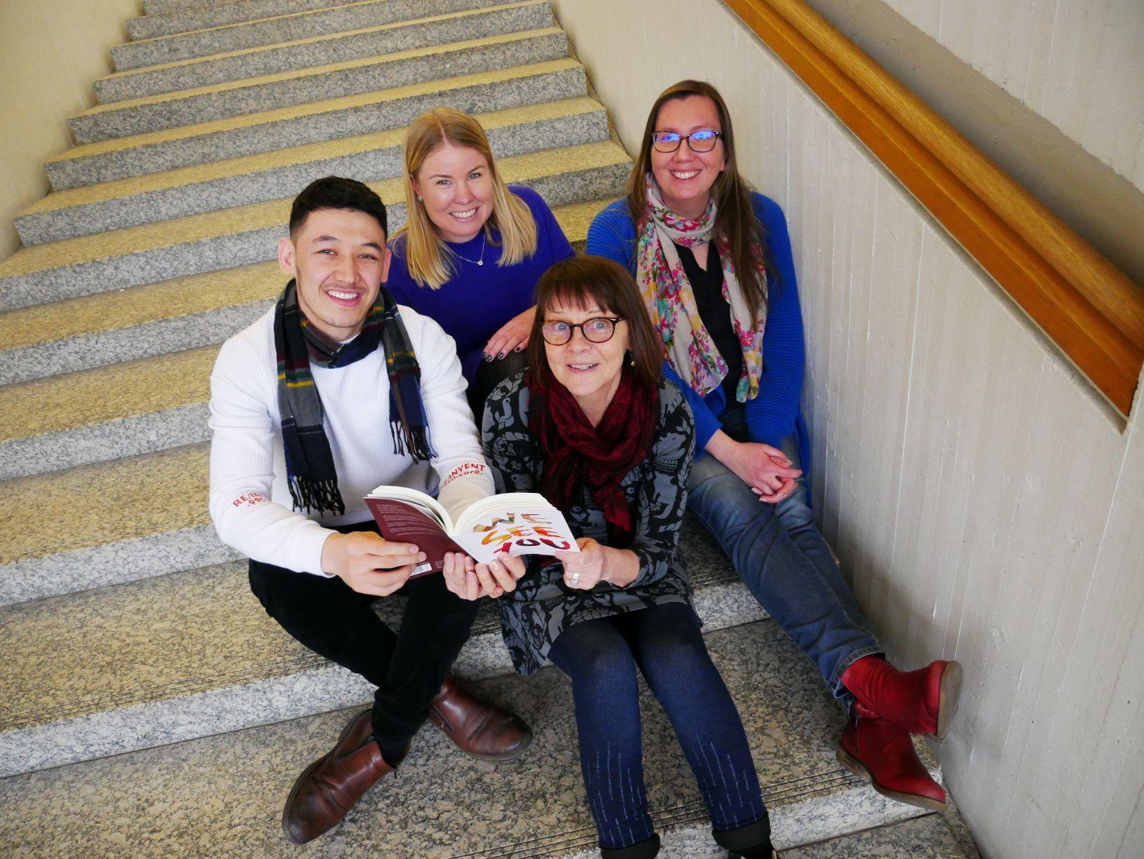 fyra personer sitter på en trappa