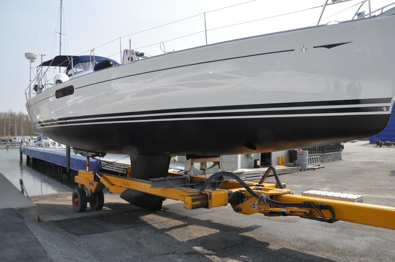 Vit segelbåt med blåmålad botten sjösätts i båthamnsjo