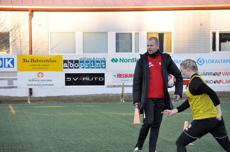 Fotbollsspelare och tränare vid en konstgräsplan