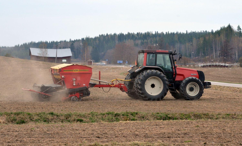 Traktor och såmaskin på dammig åker