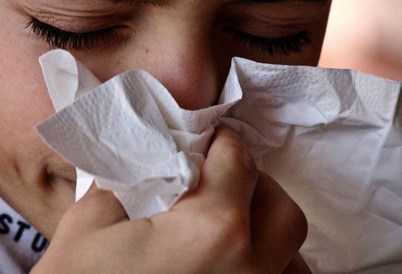 Hand håller näsduk framför näsa