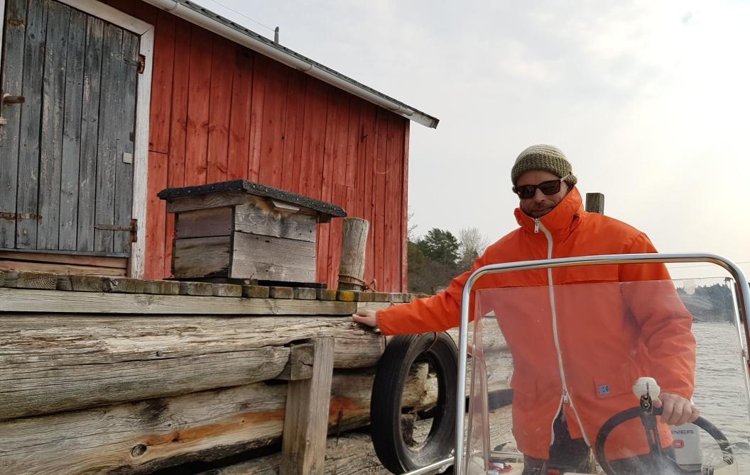 Man i båt intill en brygga. På bryggan finns en postlåda dit han levererar post.