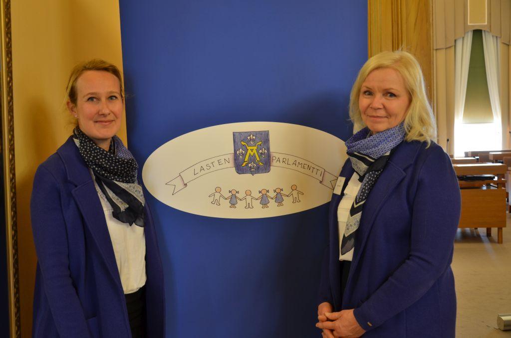 Två kvinnor står framför en skylt med texten Lasten Parlamentti.