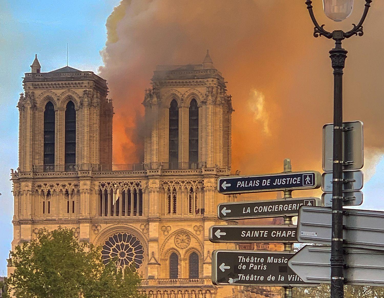 Gammal katedral brinner. I förgrunden gatuskyltar.