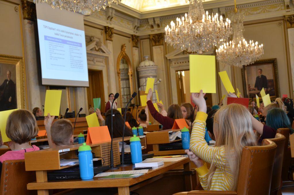 Barn deltar i omröstning genom att räcka upp gula, gröna och röda lappar.