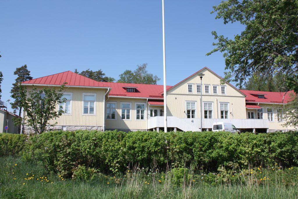 Gult hus med rött tak, grön häck framför, träd på sidan