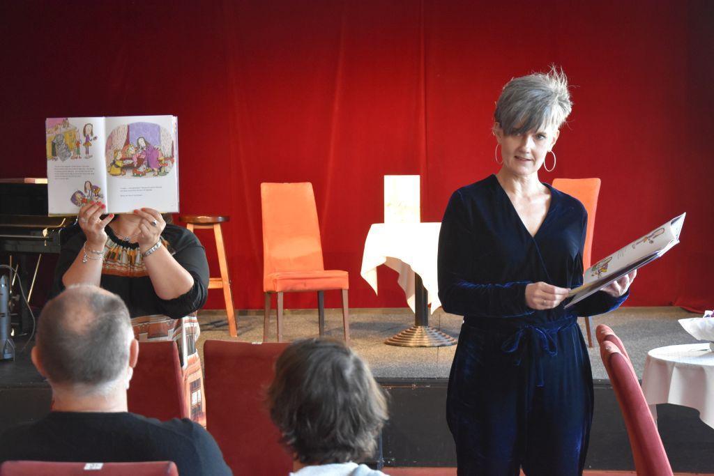Person håller öppen bok framför ansiktet, Tove Appelgren står med öppen bok i händerna och tittar mot kameran.