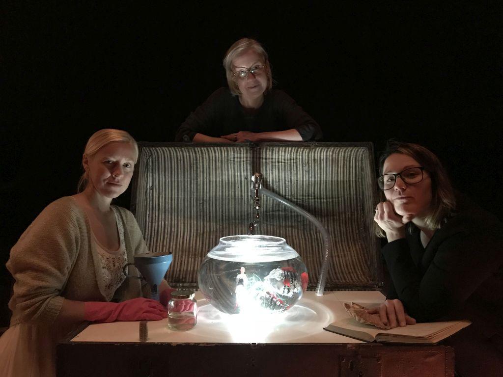 Tre personer står och sitter runt ett bord med en upplyst skål med vatten i mitten, svart bakgrund.