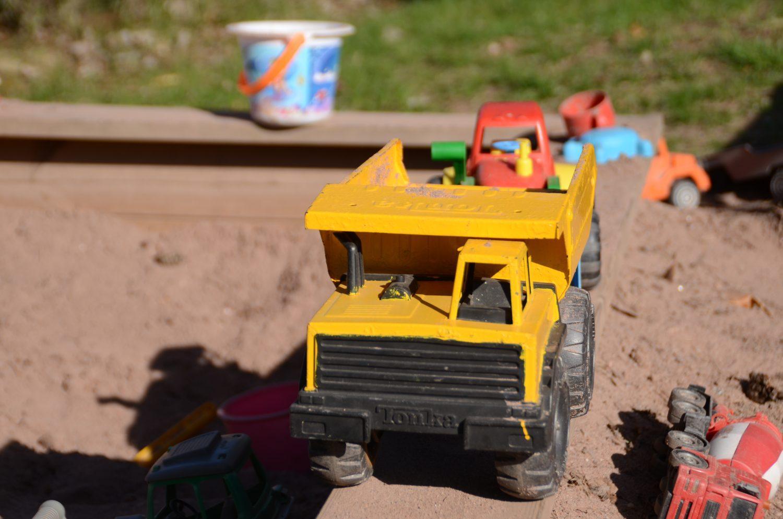 En leksakslastbil i en sandlåda.