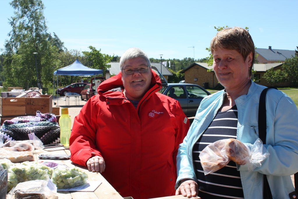 Sussi Gustafsson i röd jacka och Erna Fredriksson i ljusblå jacka, står vid ett bord med försäljningsprodukter på