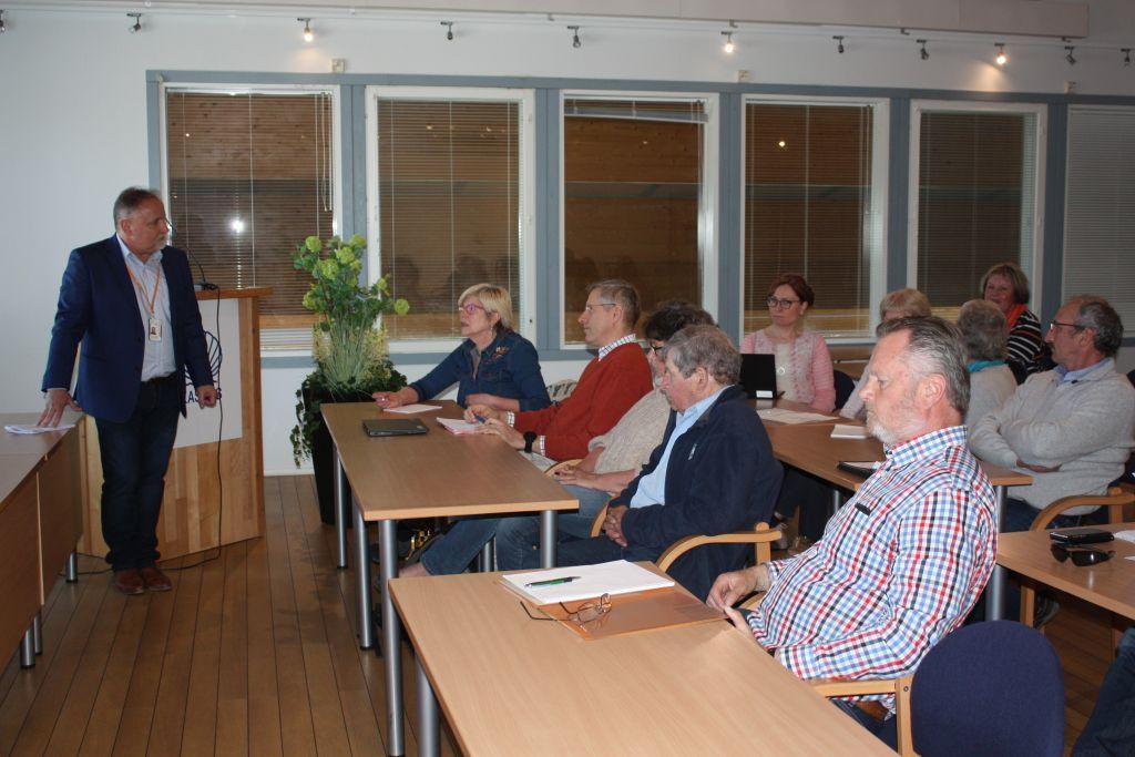 Människor som sitter vid bord i ett konferensrum. Bild tagen från sidan.