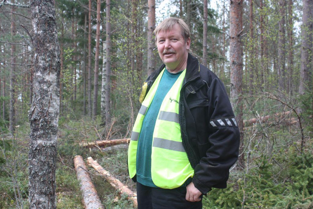 Halvbild på Kenneth Stenberg som ser in i kameran, skog i bakgrunden.