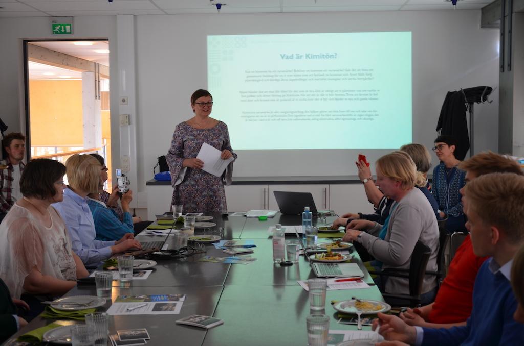 Seminarium om Kimitoöns kommun 10 år i Villa Lande. Människor sitter runt ett bord, kommundirektör Anneli Pahta säger inledningsord.