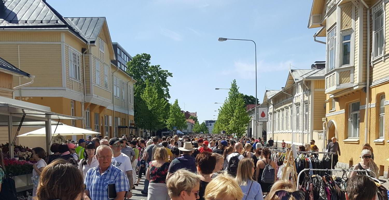 Mycket människor på en gata med trähus.