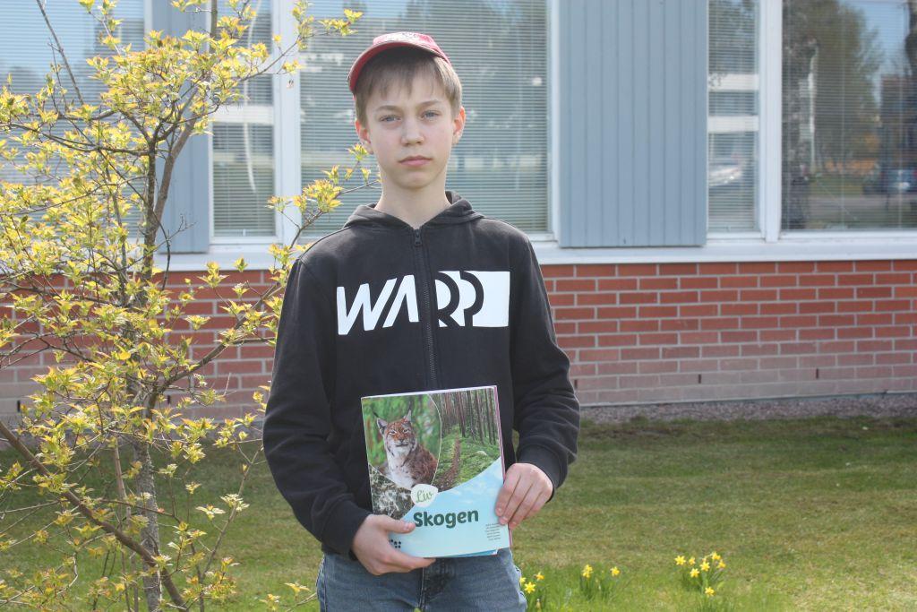 """Samuel Engblom med röd keps på huvudet, håller i sin biologi bok med titeln """"Skogen"""", i bakgrunden en buske och skolhuset."""