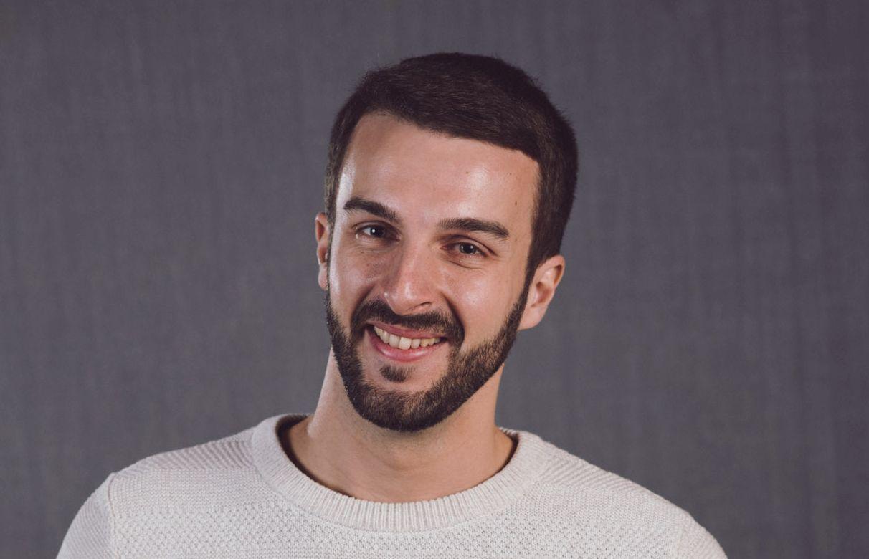 En man som leende tittar in i kameran.