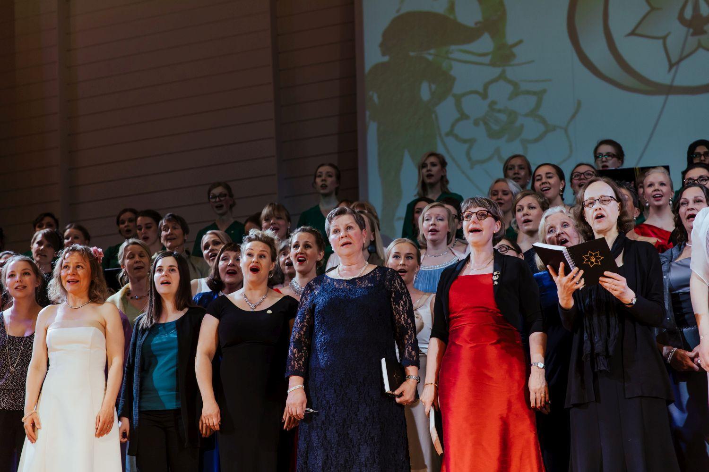 Kvinnor i festklänningar sjunger.
