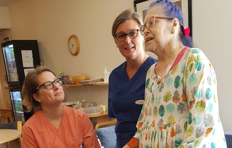 Nina Öhman (tv) och Satu Nurmela, sjukskötare på Karinahemmet i Åbo, tillsammans med patienten Maria Laitakari.