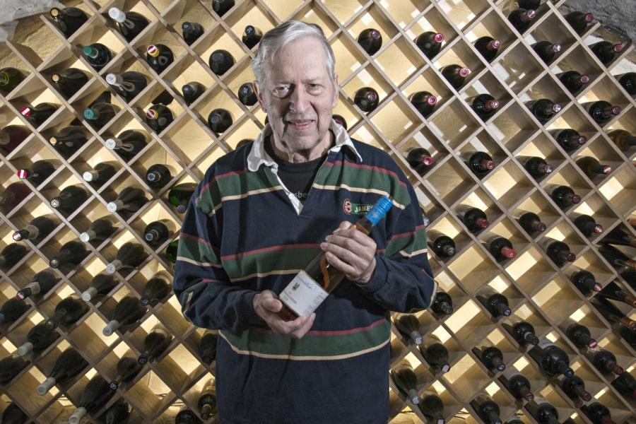 äldre man håller en vinflaska och bakom honom finns en större vinställning