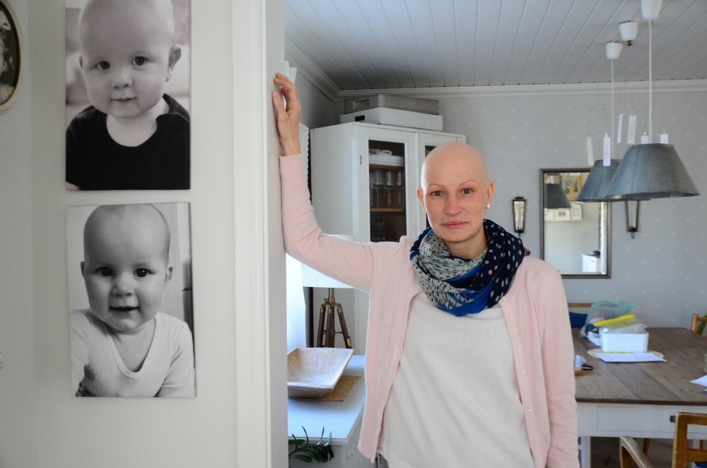 Ung kvinna utan hår tittar in i kameran. På väggen bredvid henne finns två babyporträtt, där barnen också är utan hår