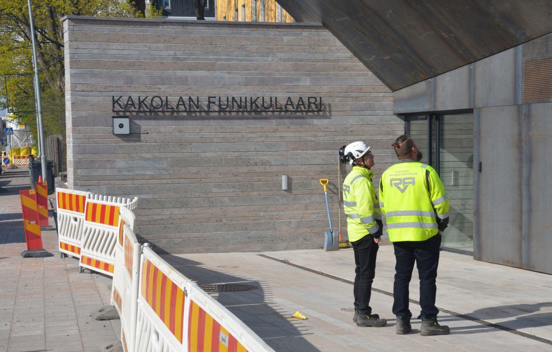 Två män i arbetskläder framför en byggnad