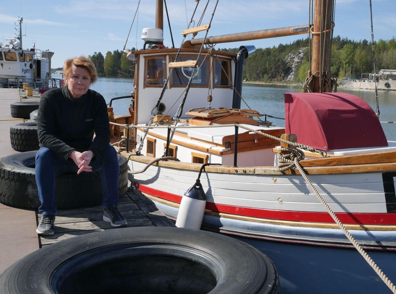 Kvinna sitter på brygga med båtar i bakgrunden