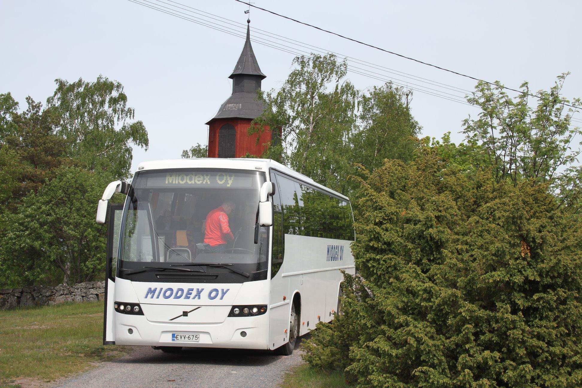 Framända på vit buss med texten Miodex, grönt buskage på sidorna, rött kyrktorn bakom bussen.