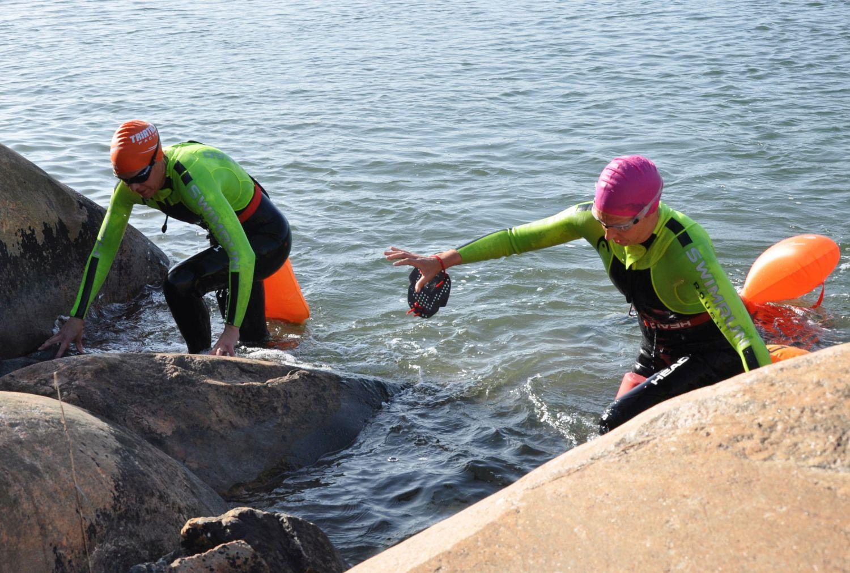 Två kvinnor klättar upp ur havet på strandklippa