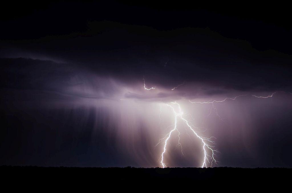 en blixt slår ner från en lila himmel