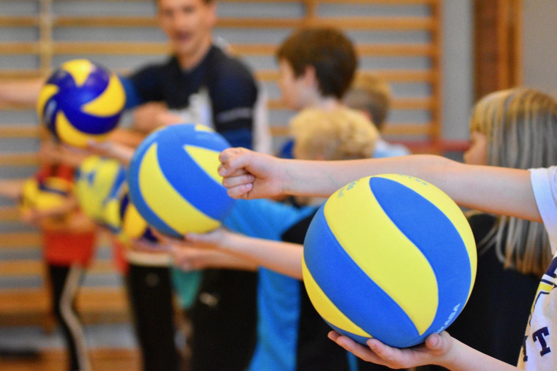 Barn tränar volleyboll i gymnastiksal.