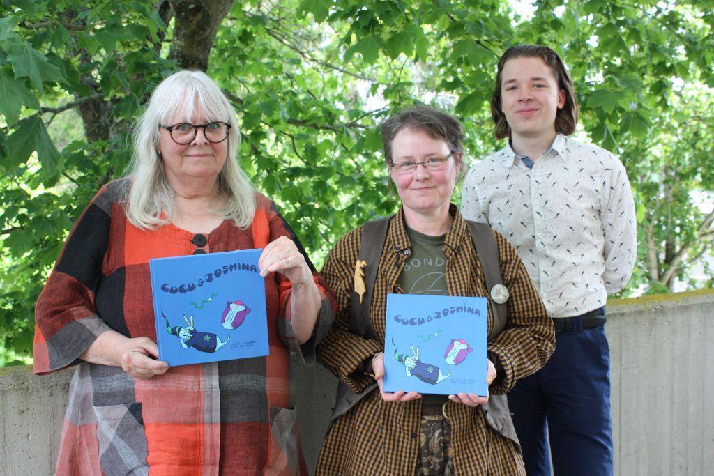 Tre personer står och ler in i kameran, Eivor Lindgård och Satu Zwerver med varsin blå barnbok i händerna, i bakgrunden ett grönt lövträd