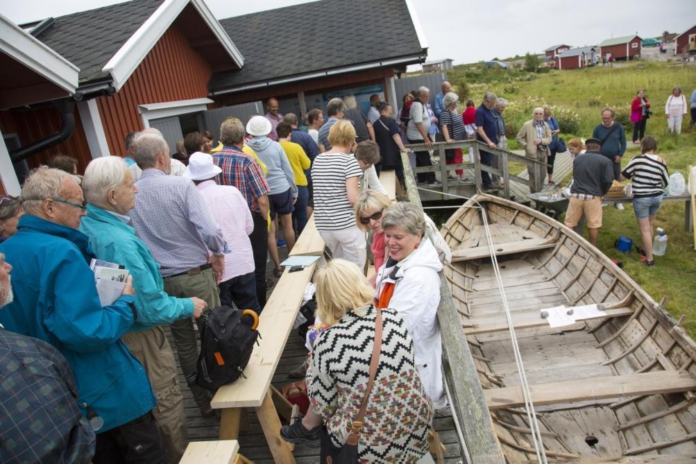 Folksamlingr vid ett båthus