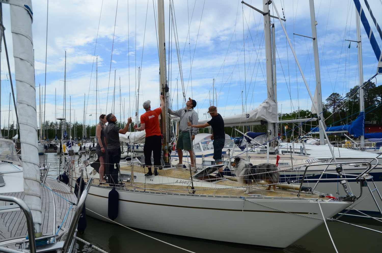 Männsikor står och tittar på en mast ombord på en segelbåt.
