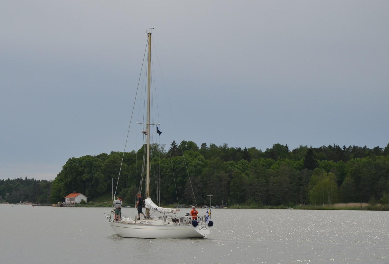 Segelbåt går för motor på en fjärd.