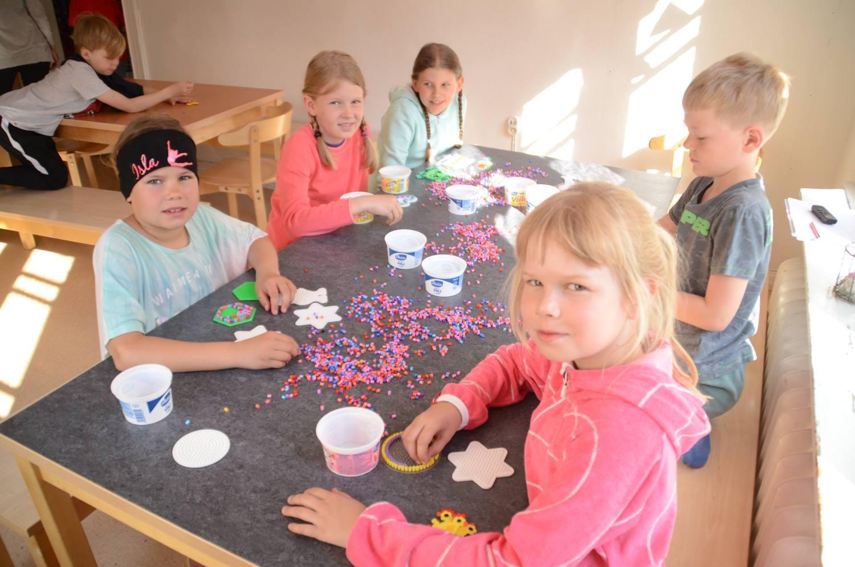 Barn sitter runt ett bord med pärlor.