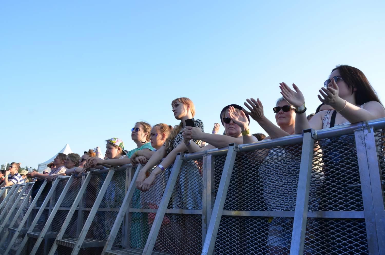 Människor applåderar och hänger över ett staket.