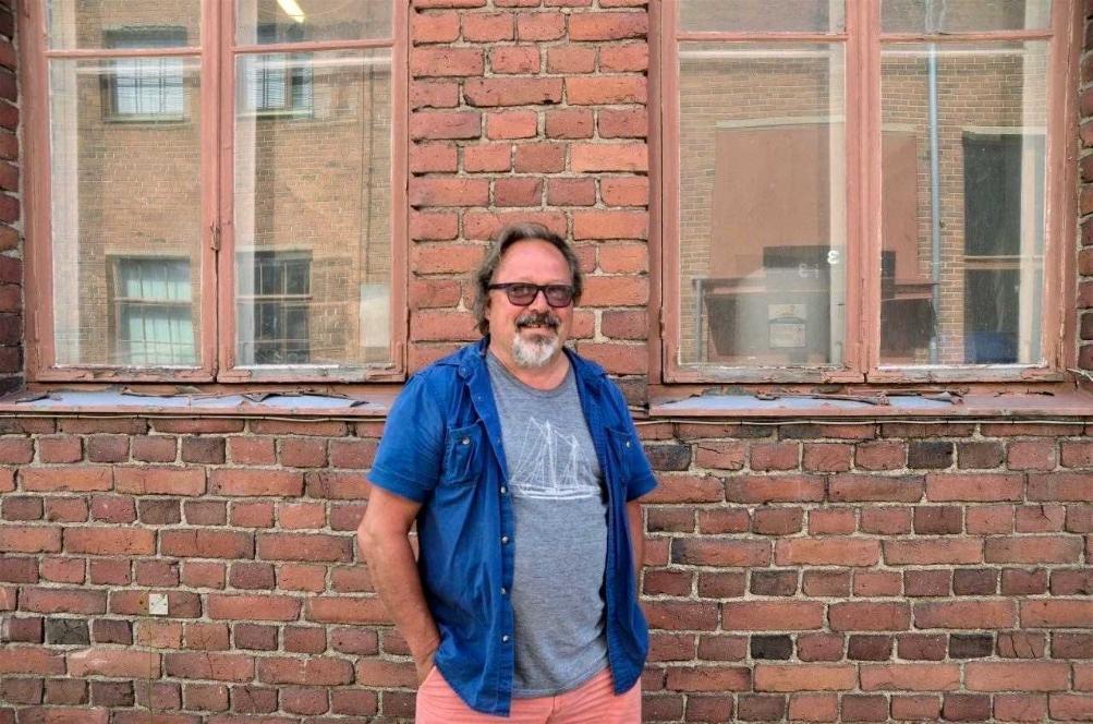 Dick Holmström framför röd tegelvägg