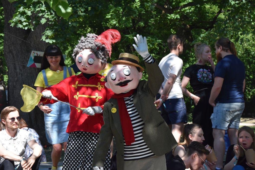 Två personer utklädda till lustiga dockor poserar på ett festivalområde.